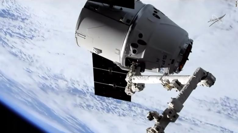 Giant robotic arm catches SpaceXs Dragon cargo spacecraft