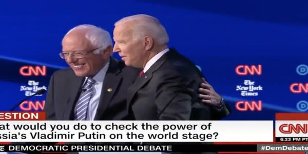 Joe Biden and Bernie Sanders share a jovial hug on the Democratic debate stage