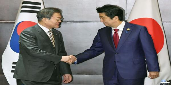 Japans Abe asks South Koreas Moon to act on row at first meeting for 15 months