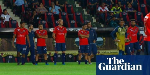 Players protest unpaid wages by standing still in Mexican football match – video