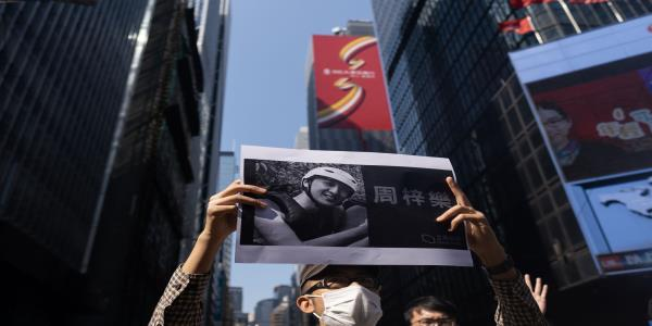 Hong Kong Officer Fires Warning Shot After Death Fuels Protests
